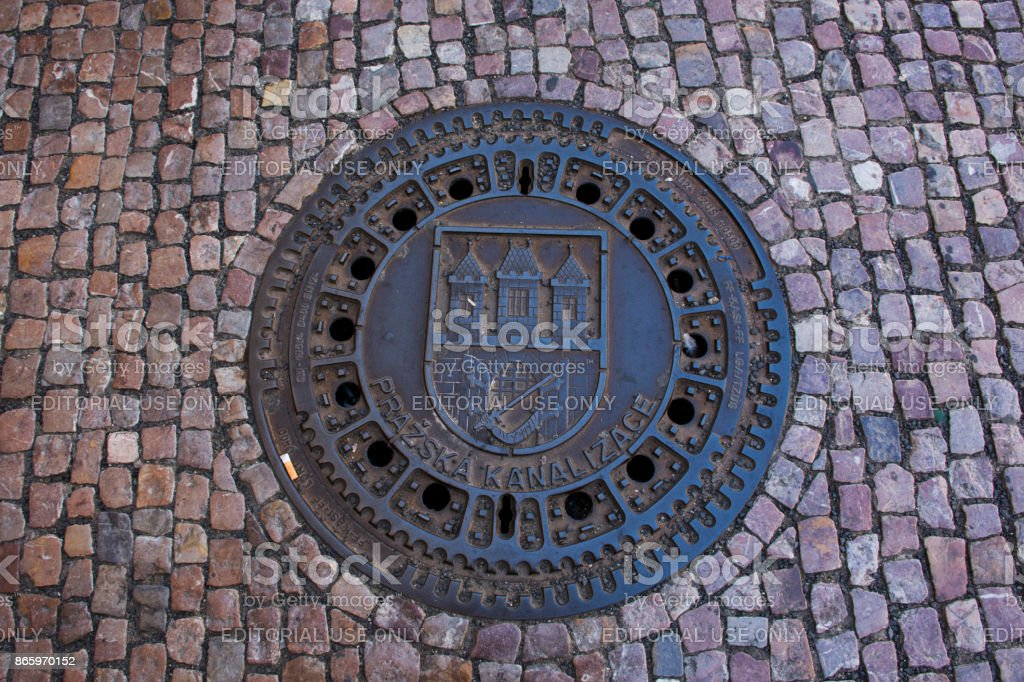 Art Design Symbol Of Prague City On Manhole Cover At Footpath Beside