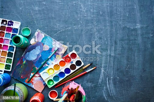 Paints and paintbrushes on table