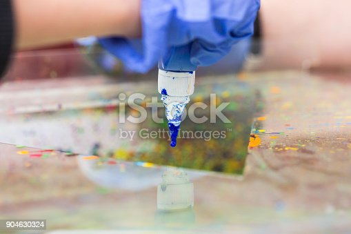 istock art equipment, tools, crafting concept. close up of the tip of tube of acrylic paint, that is smeared with blue paint, arms of artist in blue work gloves are holding it carefully 904630324