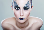 beautiful female model with art fantasy make up face paint
