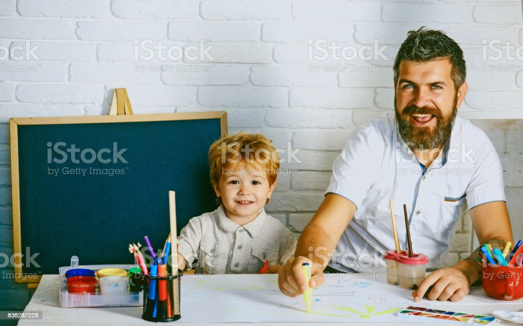 Art for children. Bearded adult father teaches to draw little son in...