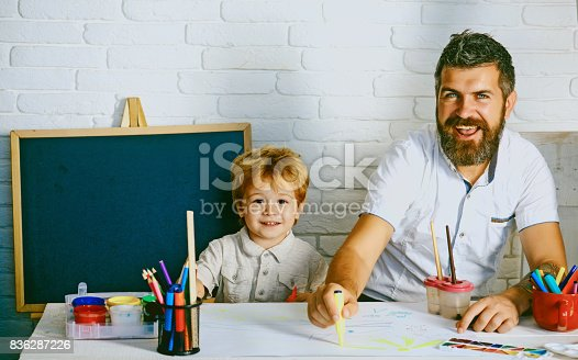 istock Art for children. Bearded adult father teaches to draw little son in studio. Boy and man draw picture. Creative education and art, development in kindergarten. Childhood with parents talented teacher 836287226