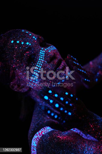 Art girl cosmos in ultraviolet light. Woman does yoga, body warm-up. Entire body is covered with colored droplets. Astral yoga. Noise, out of focus