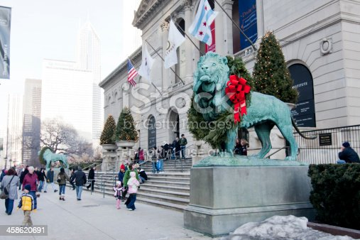 Chicago, IL, USA - January 2, 2009:  Art Institute of Chicago at Christmas time.  The two bronze lions which guard the entrance are decorated with wreaths with large red bows.  Tourists are bustling about on a cold winter day.