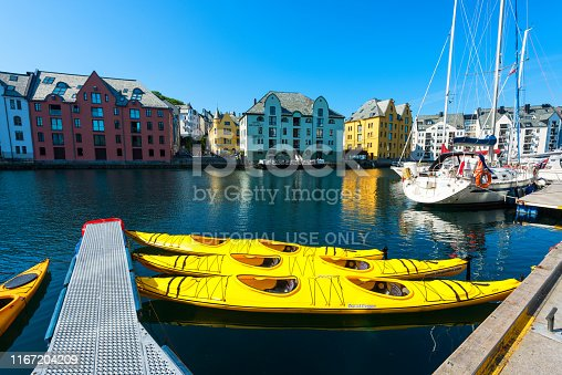 istock Art Nouveau architecture of Alesund town, Norway. Row of yellow kayaks in the water. 1167204209