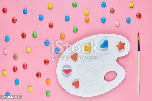 Art of sweetmeats concept. Sweet candy in paint palette on pink background. Love to colorful sweetmeats in childhood and cooking sweets