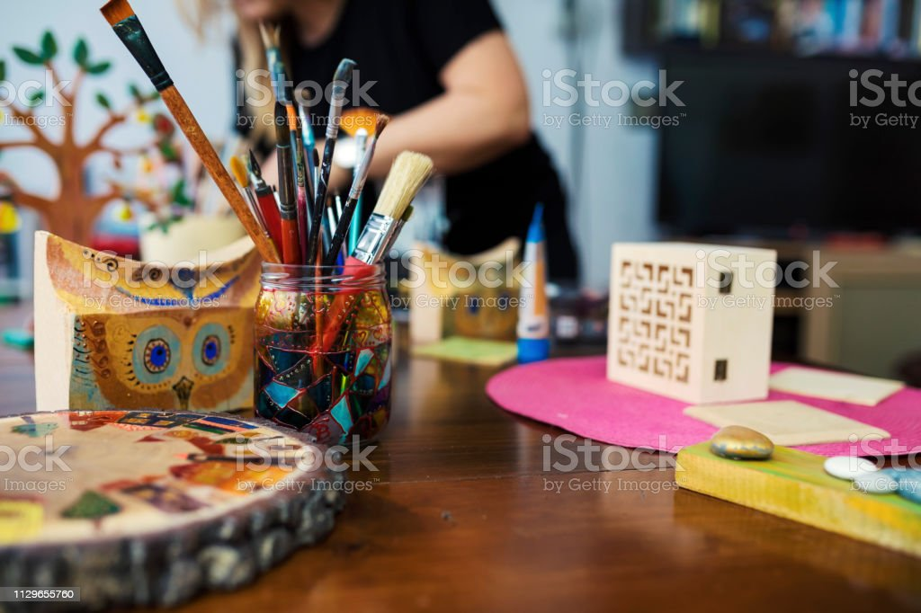 Artist mature woman painting on a wooden box in her art studio