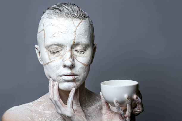 Art portrait of woman covered in clay stock photo
