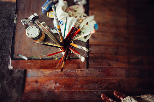 Art studio wooden table with paintbrushes paint tubes and rag