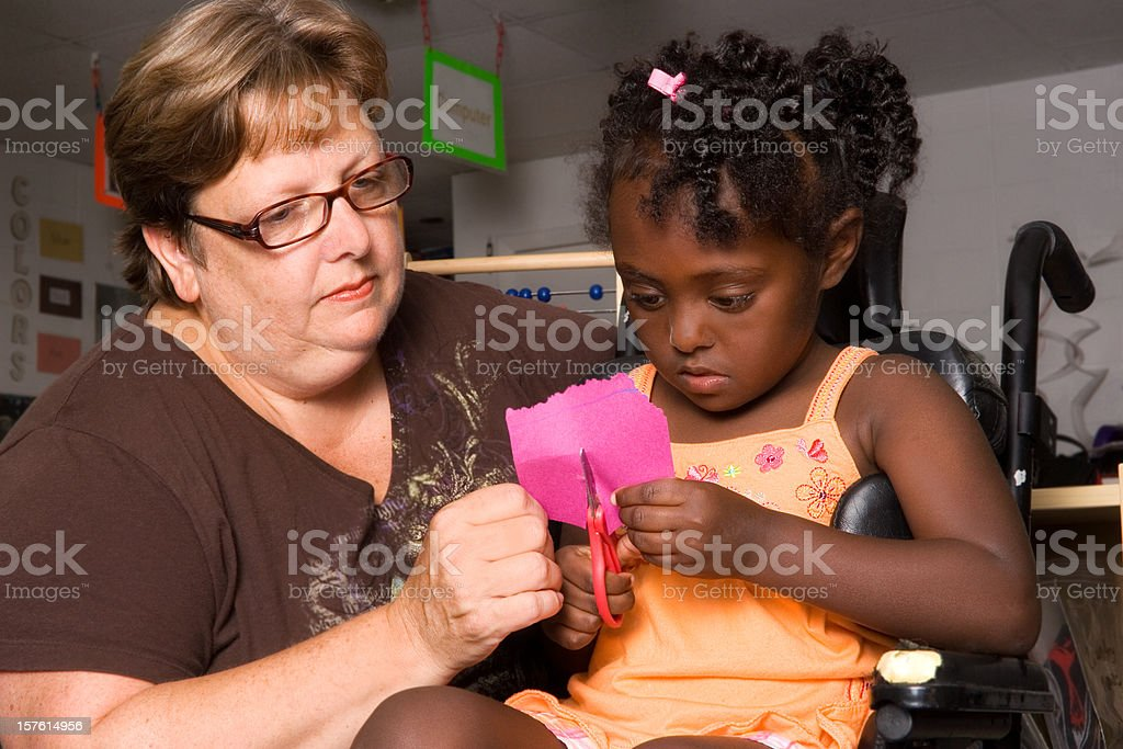 Art teacher assists little girl in wheelchair stock photo