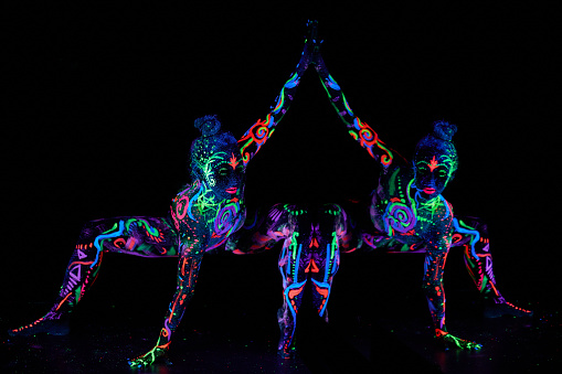 Art woman body art on the body dancing in ultraviolet light. Bright abstract drawings on the girl body neon color. Fashion and art woman