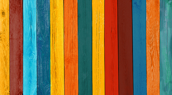 Art Wooden Background. Creative Colorful Wallpaper. Restored old wooden Texture. Wood Surface Fence Panel with boards painted Multicolored Paint, Close-up. Wide Horizontal Image with Copy Space