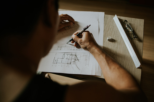 Close-up of Architect designer man while sketching and design house for the customer, Bangkok Thailand