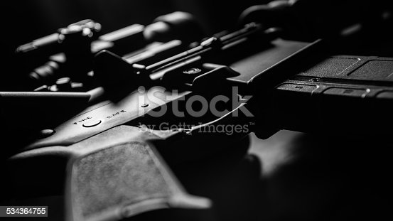 High contrast black and white AR-15 close-up with selective focus on Safe / Fire receiver stamping.
