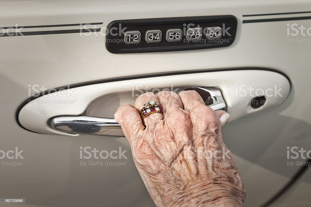 arthritic hand of senior woman opening car door royalty-free stock photo