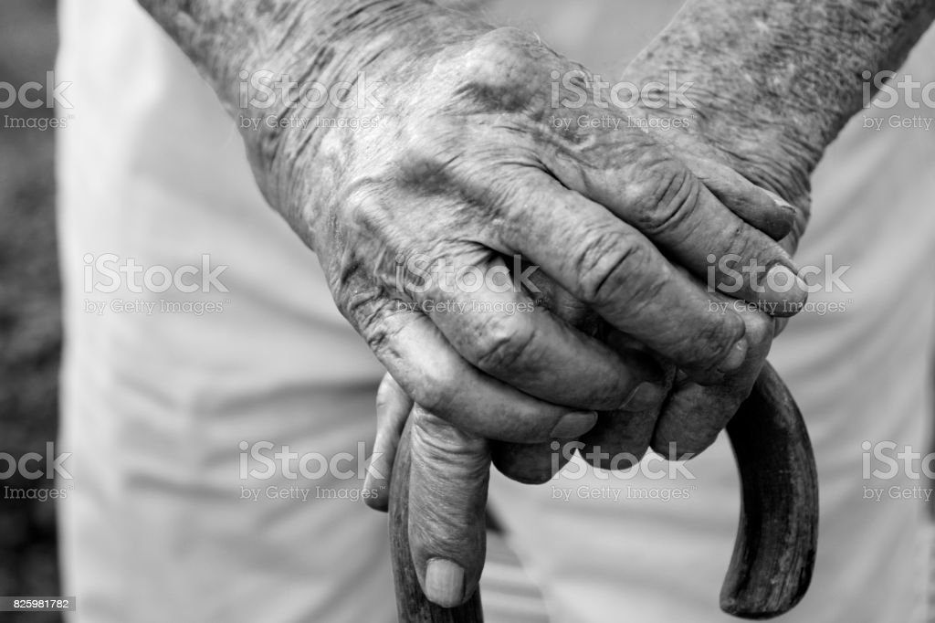 Arthritic Hands on cane, black and white photograph. Looking down view at hands stock photo