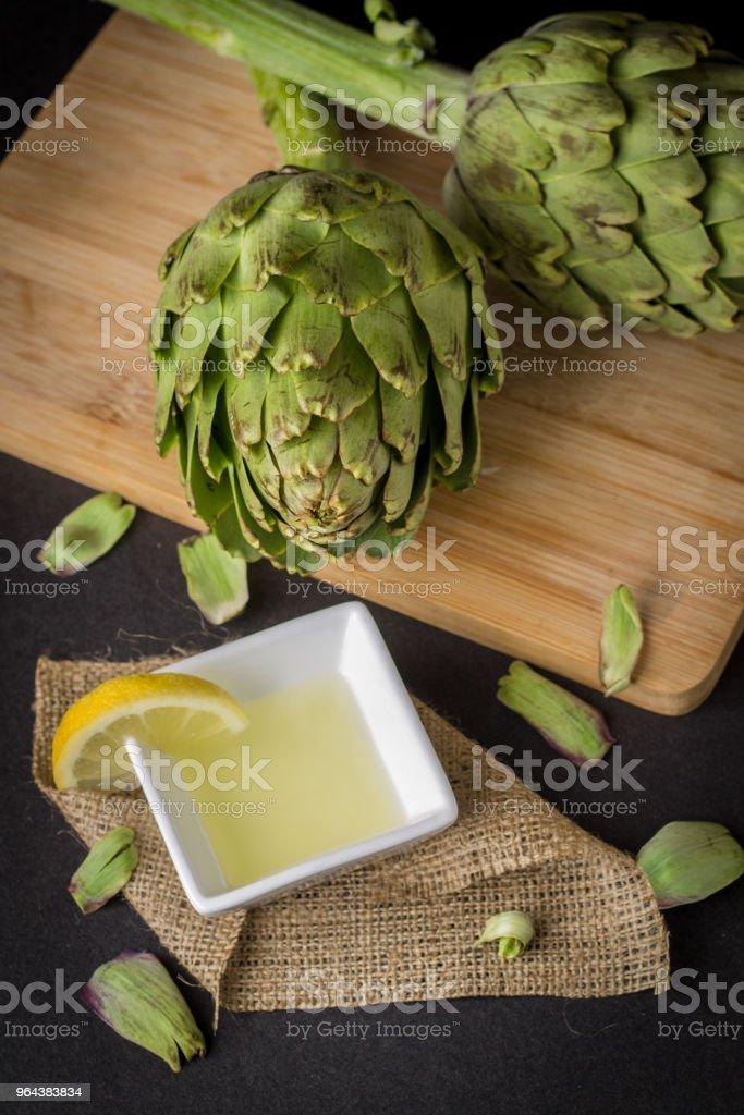 Alcachofra e suco de limão sobre a mesa de madeira - Foto de stock de Alcachofra royalty-free