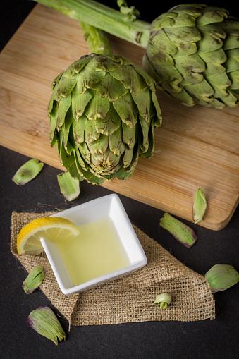 Foto de Alcachofra E Suco De Limão Sobre A Mesa De Madeira e mais fotos de stock de Alcachofra