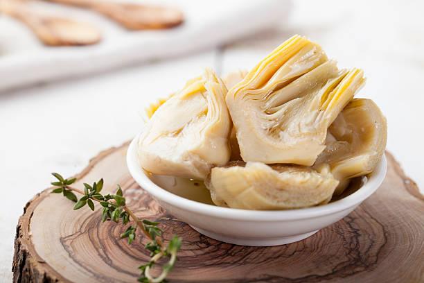 Cuore di carciofo marinato in olio d'oliva una piccola ciotola bianca - foto stock