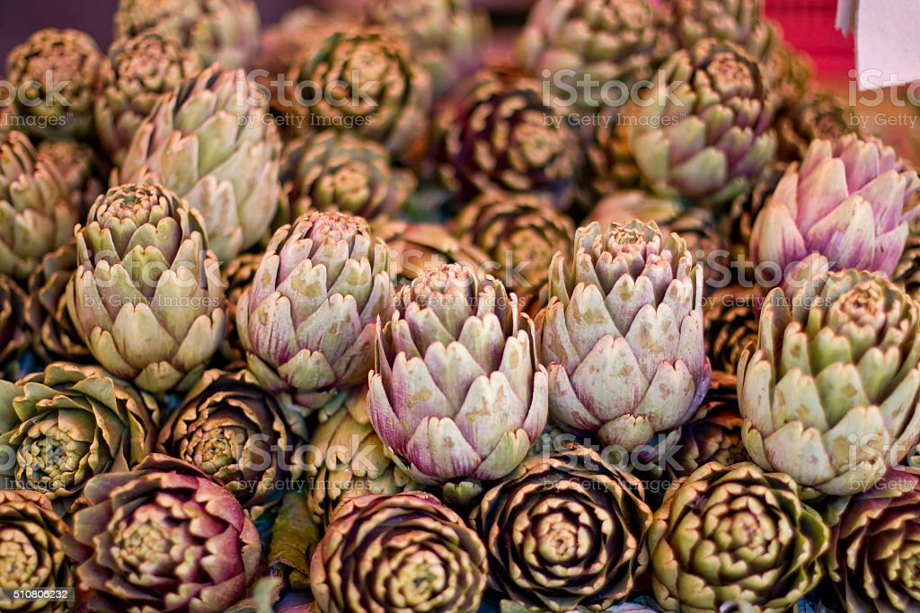 Artichoke in a street market in Catania, Sicily Fresh artichoke (lat. Cynara cardunculus) Edible flower just before it blooms on the street stall in Vegetable market in Catania, Sicily Island, Italy. Artichoke Stock Photo