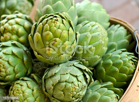 Fresh artichokes in a basket for sale at a market. (SEE LIGHTBOXES BELOW for more organic spring vegetables, fruits, meals & food backgrounds...)