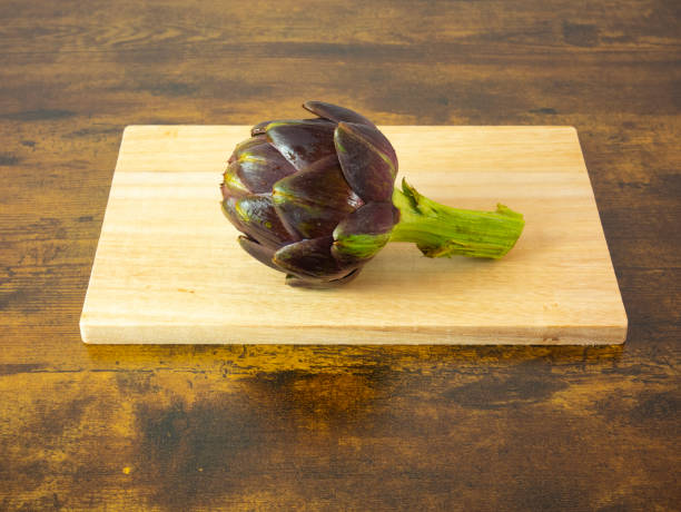artichoke on cutting board on the table, still life of vegetables, ingredients for vegetarian recipe stock photo