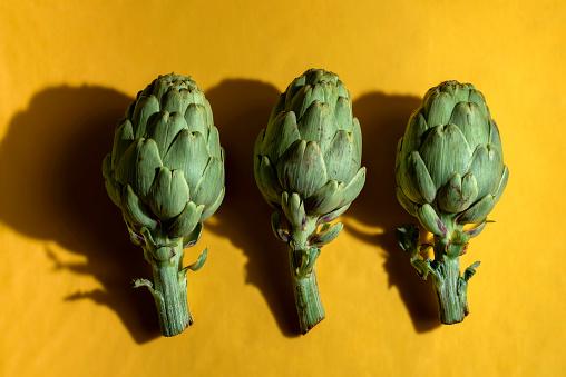 Three Artichokes (Cynara scolymus) isolated on yellow background