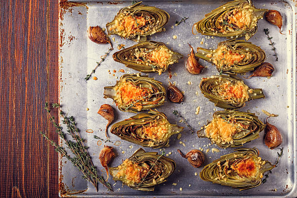 artichokes baked with cheese, garlic and thyme. - bakplåt bildbanksfoton och bilder
