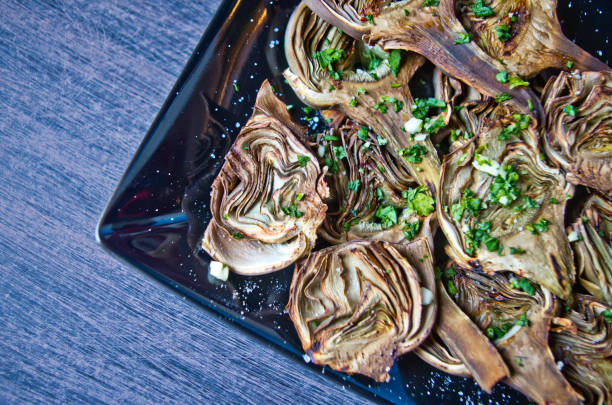 artichokes baked with oil, parsley and lemon stock photo