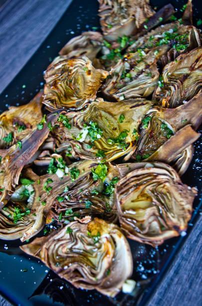 Carciofi al forno con olio, prezzemolo e limone - foto stock