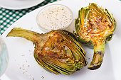 Delicious roasted  halves of artichokes served with coarse salt  on plate