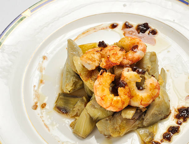Artichokes with prawns sauteed and caramelized onions stock photo