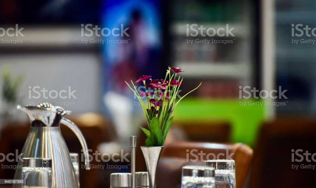 Artificial flowers kept on a dinning table in a food court stock photo