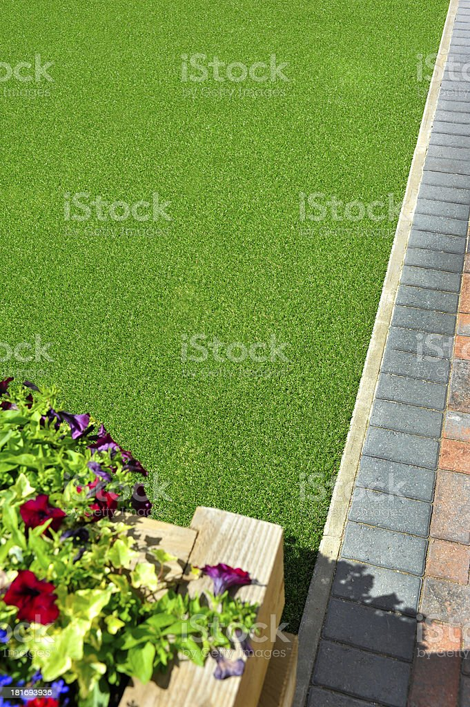 Artificial grass and flowers stock photo