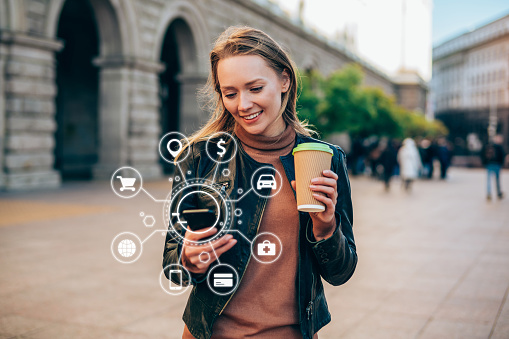 Beautiful young woman using a smartphone with various icons of smart technology.
