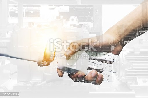 istock Artificial intelligence and robotic concepts. Industrial 4.0 Cyber Physical Systems concept. Double exposure of Robot and Engineer human holding hand with handshake and automate machine background. 857233806