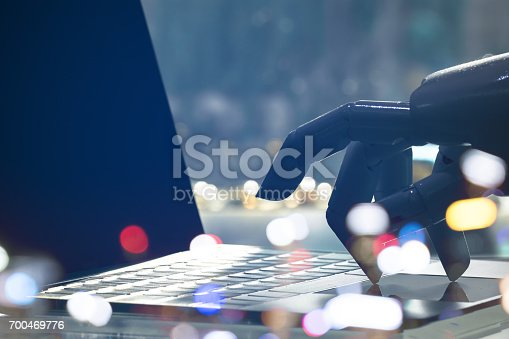 istock Artificial intelligence , chatbot , cyber communication , robot world and robo advisor. Robot finger point to laptop button with bokeh background. 700469776
