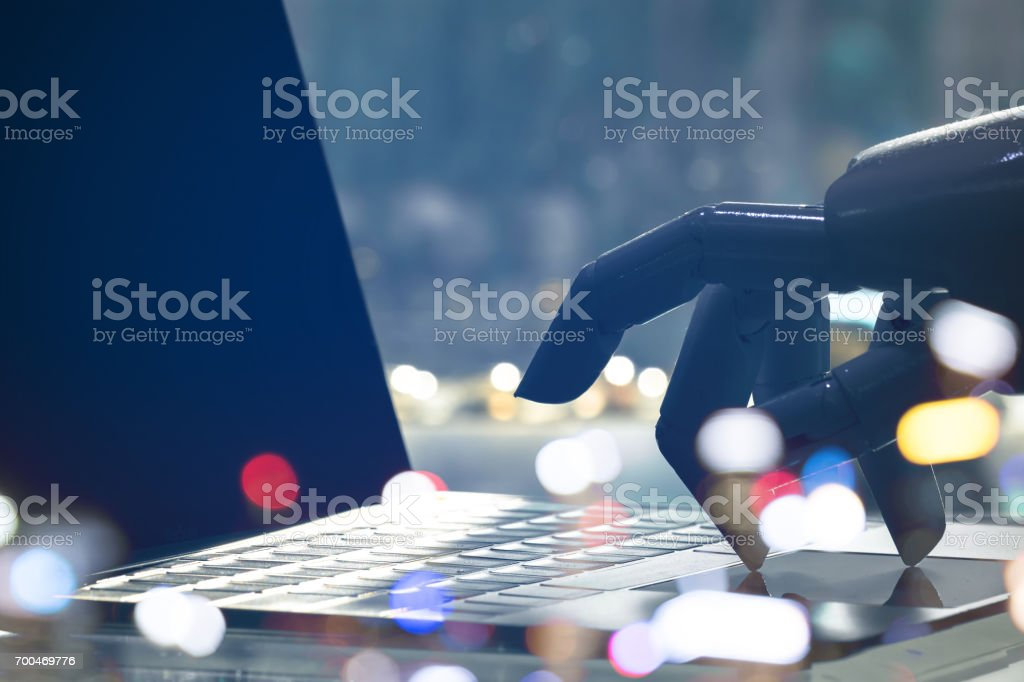 Artificial intelligence , chatbot , cyber communication , robot world and robo advisor. Robot finger point to laptop button with bokeh background. stock photo