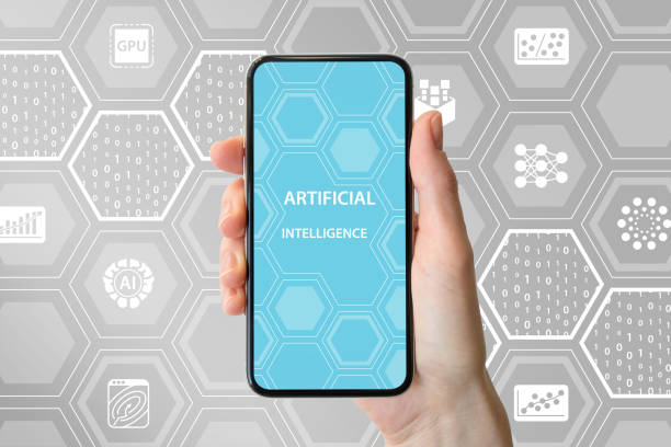 AI / artificial intelligence concept. Hand holding modern frameless smartphone in front of neutral background with icons stock photo