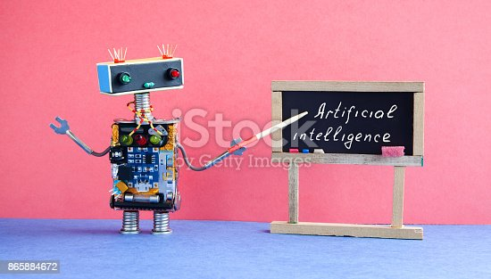 istock Artificial intelligence concept. Robot teacher explains modern theory. Classroom interior with handwritten quote on black chalkboard. Pink blue colorful background 865884672