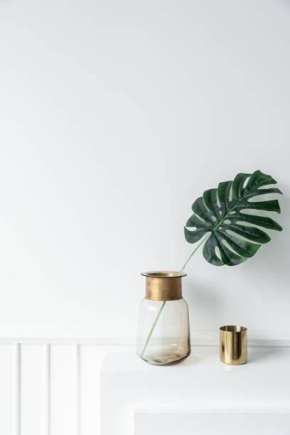 kunstpflanze in glasvase mit goldrand edelstahl trim und gold spiegel vase auf leeren kamin im modernen minimalistischen stil / gemütliche innenraum-konzept / leeren raum fo advrtisement - vase glas stock-fotos und bilder
