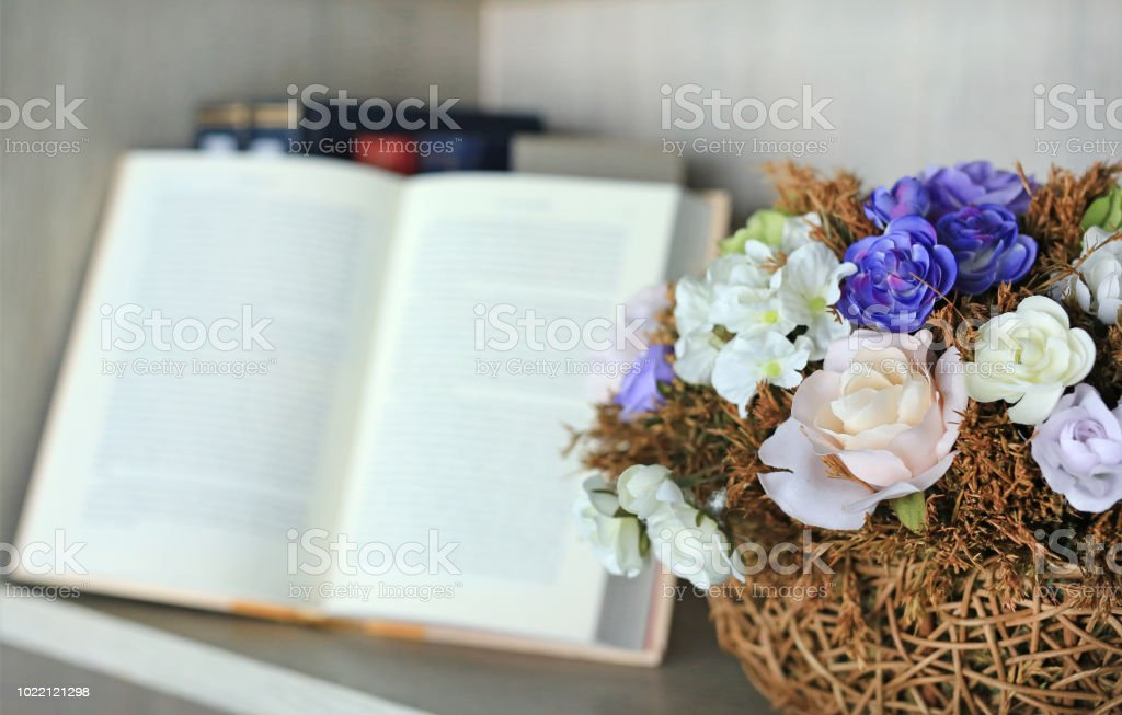 Artificial Rose Flower In Basket On The Bookshelf Library Against Blur Of Open Hardcover Book