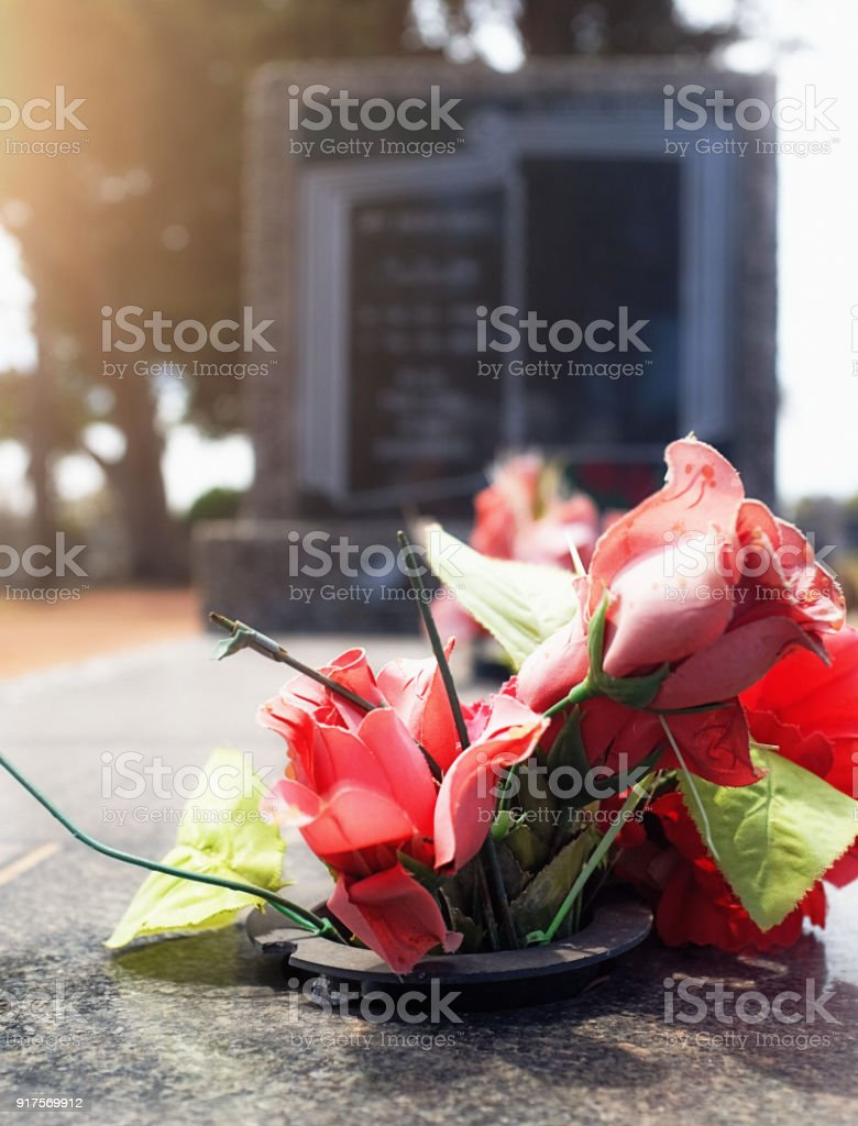 Artificial roses decorate a gravestone stock photo