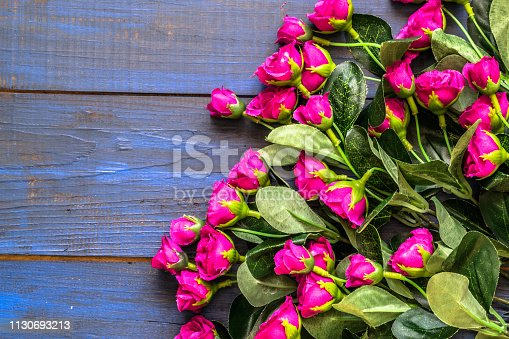 680461500istockphoto Artificial roses on wooden background. Mothers day card. 1130693213