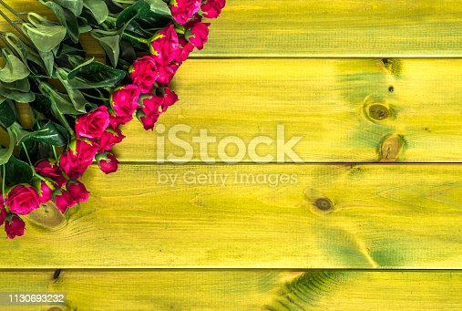 680461500istockphoto Artificial roses on wooden background. Mothers day card. 1130693232