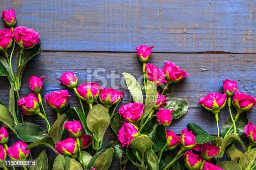 680461500istockphoto Artificial roses on wooden background. Mothers day card. 1130693315