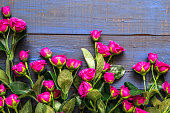 istock Artificial roses on wooden background. Mothers day card. 1130693315
