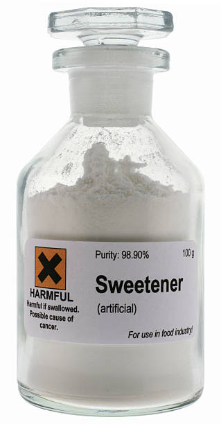Artificial sweetener on glass container with warning sign stock photo
