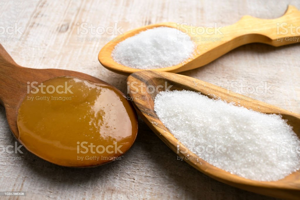 Artificial Sweeteners and Sugar Substitutes in wooden spoons. Natural and synthetic sugarfree food additive:  sorbitol, fructose, honey, Sucralose, Aspartame stock photo