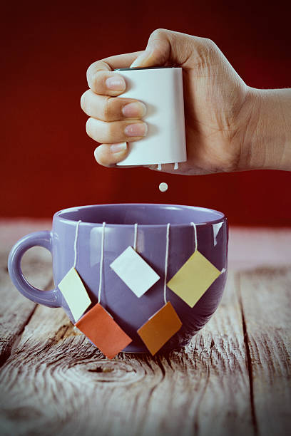 Artificial sweetner being added to a mug of tea. stock photo